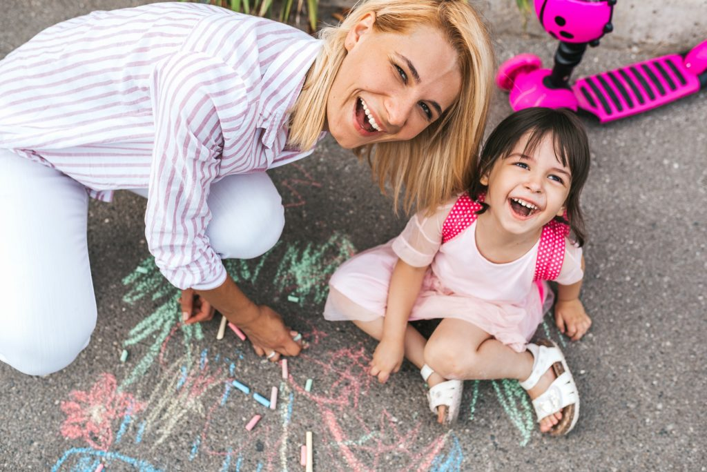 Mom with daughter playing with sidewalk chalk